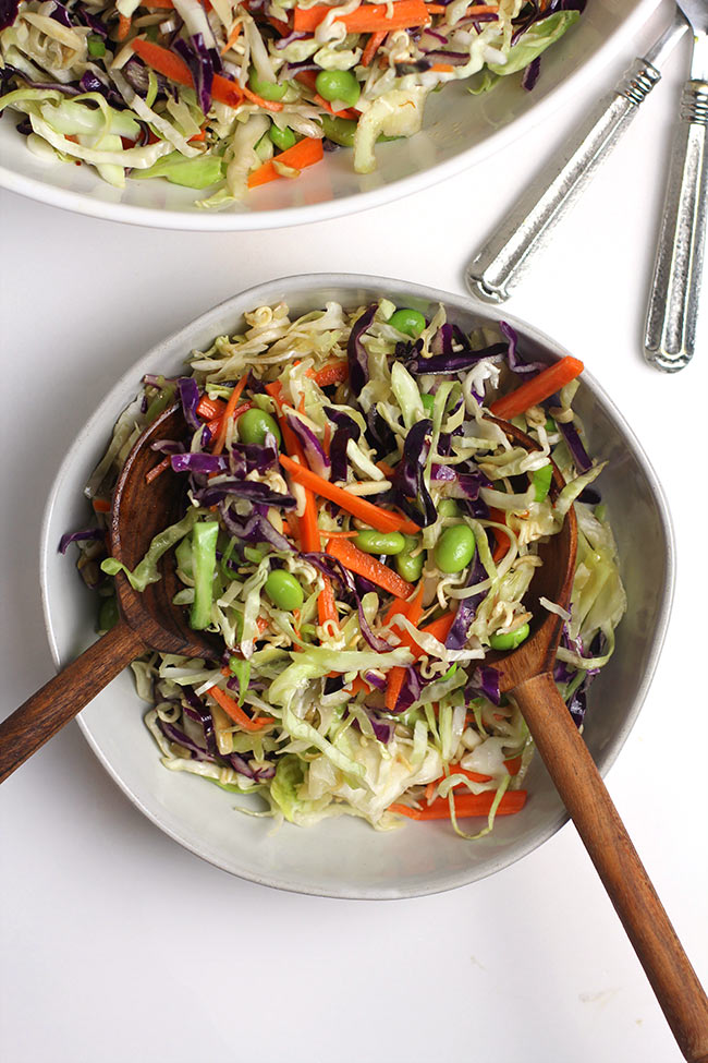 A white serving bowl of asian cabbage salad, with two wooden spoons serving it.