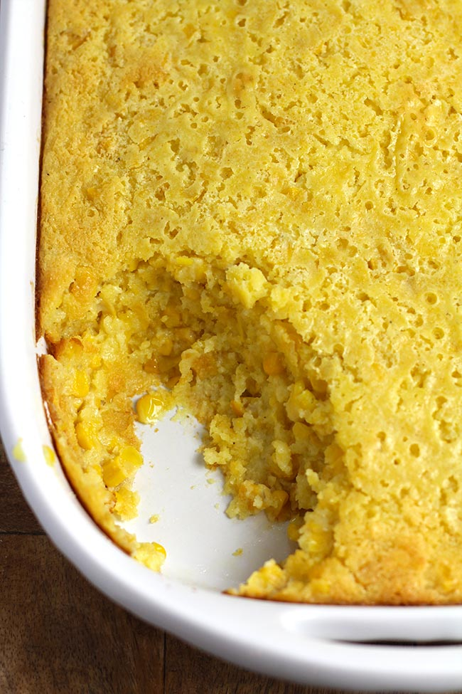 Close up shot of a portion of a creamy corn casserole, with a scoop missing.