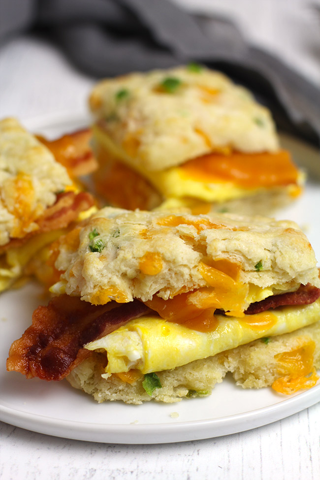 Side shot of a white plate of three jalapeño cheddar biscuit egg and bacon sandwiches.