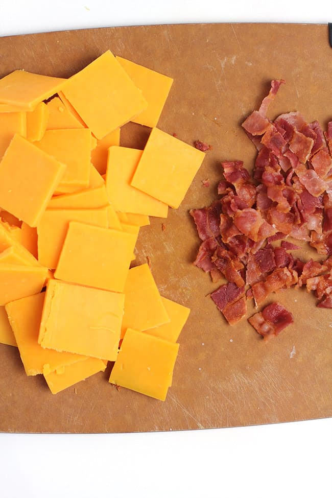 A cutting board with thinly sliced cheese and crumbled bacon.