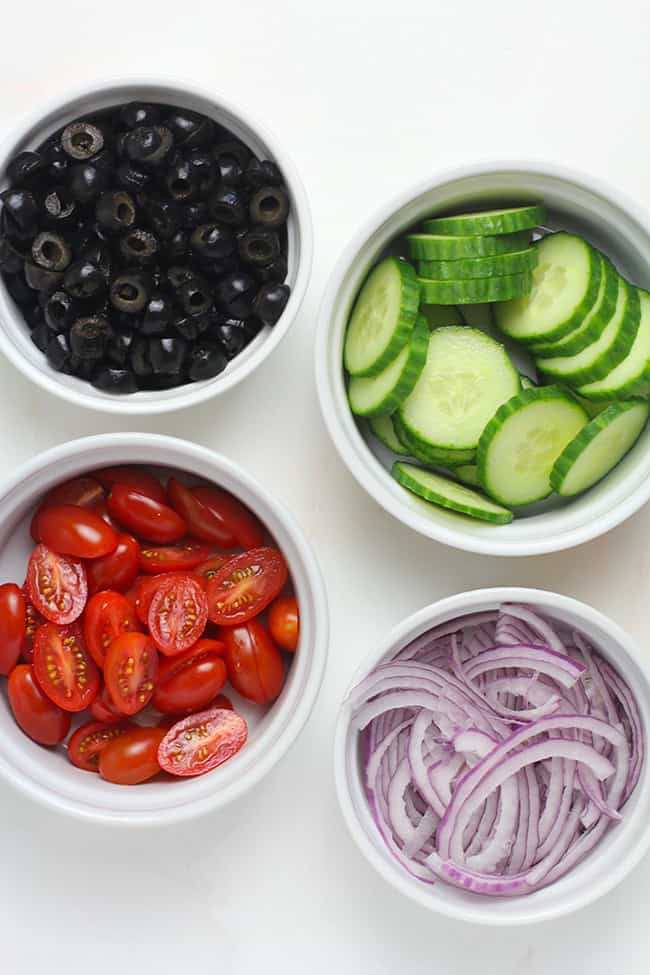 Small bowls of olives, cucumbers, tomatoes, and red onion.
