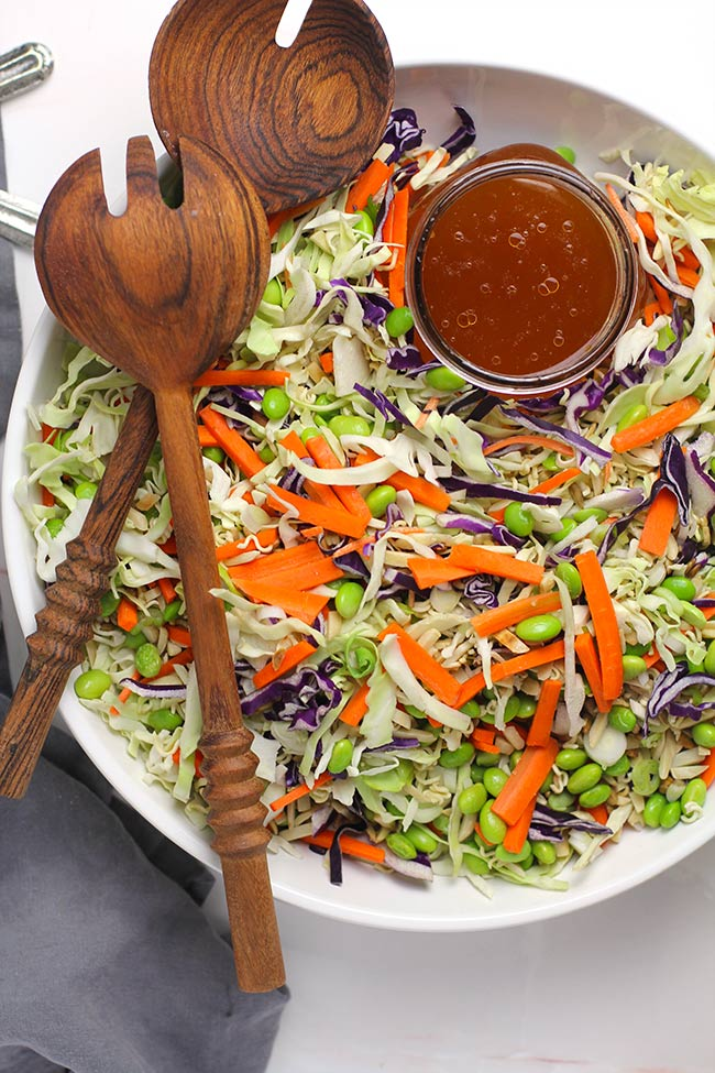Overhead view of a large white bowl of crunchy asian cabbage salad, with a jar of dressing and wooden spoons.