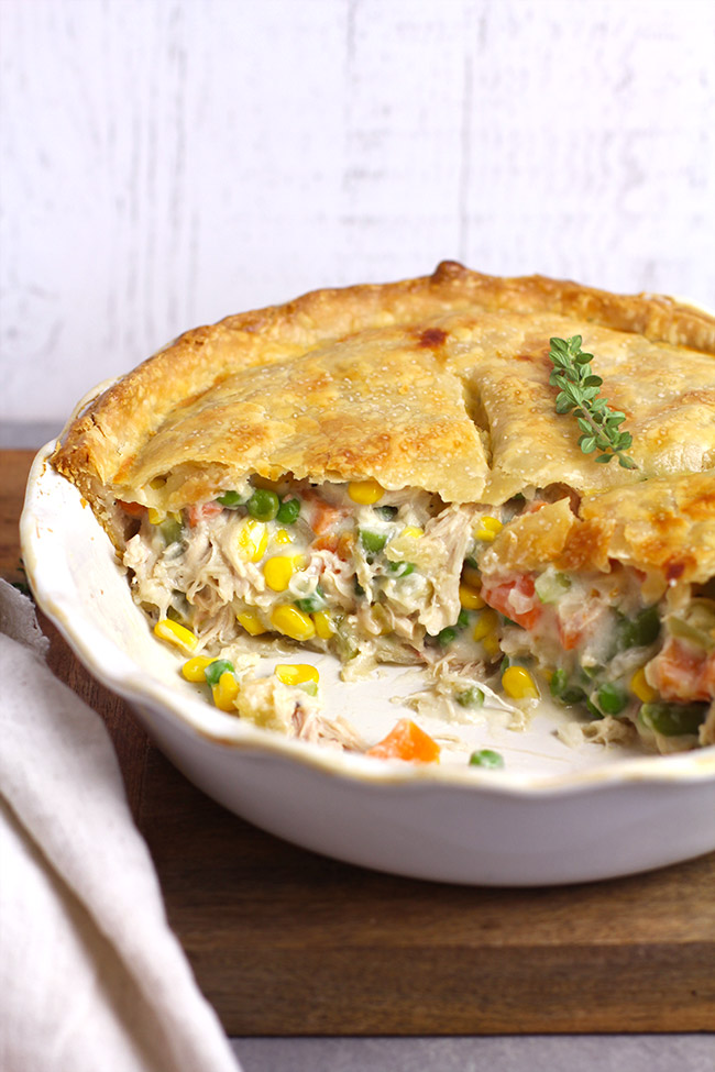 Side view of a partial chicken pot pie, with the filling showing.