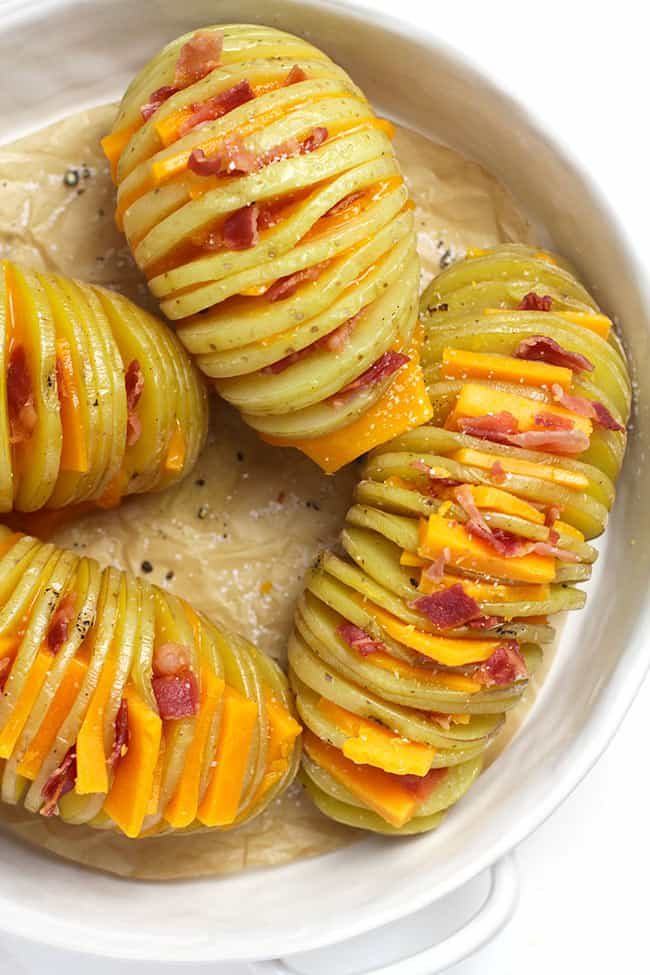 The hasselback potatoes before baking, with slices of cheese and bacon.