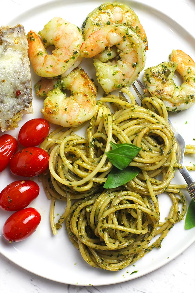 A white plate with a serving of shrimp pesto pasta, with sautéed tomatoes and focaccia.