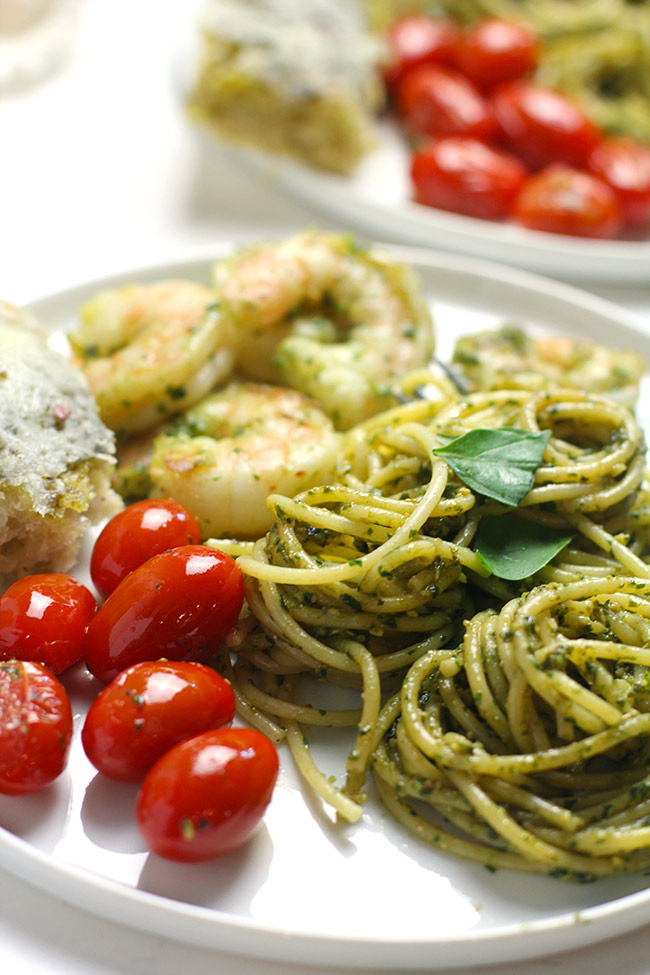 Side view of a white plate with a serving of shrimp pesto pasta, with sautéed tomatoes and focaccia.