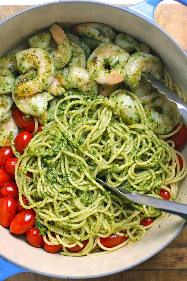 A stock pot of the shrimp pesto sauce, with the noodles combined with the sauce.