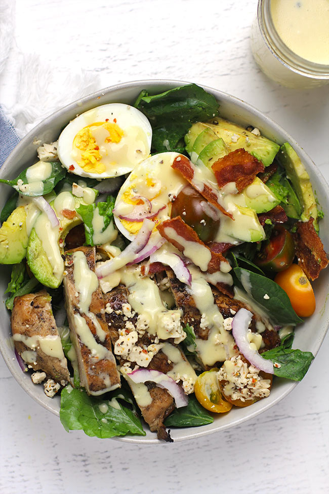 A serving of grilled chicken Cobb Salad with honey mustard dressing.