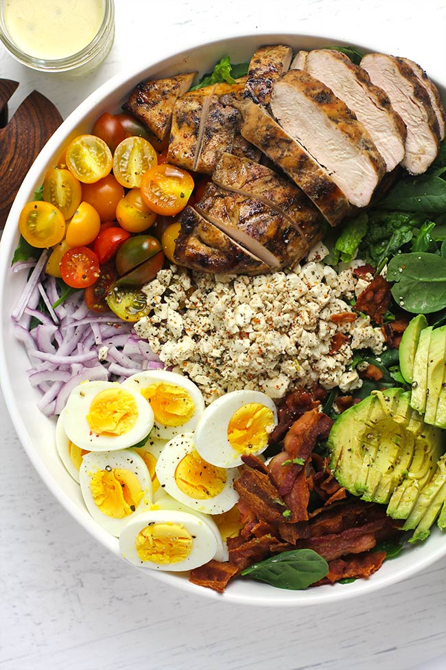 A large serving bowl full of ingredients for grilled chicken Cobb salad.
