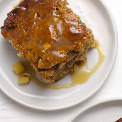 Overhead shot of two servings of apple cake, with caramel sauce on top.