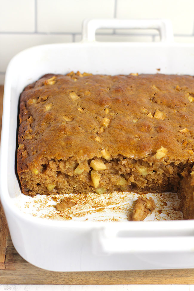 A side view of a partial  dish of apple cake, showing the apples inside.