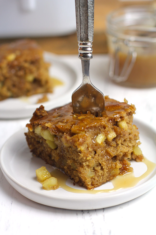 Side shot of a piece of apple spice cake with caramel sauce.