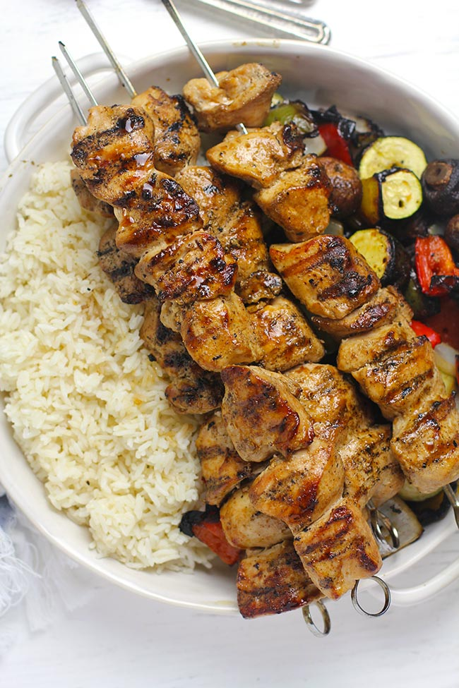 Overhead shot of a white bowl filled with rice and veggies, topped with grilled chicken skewers.