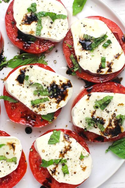 A partial plate of caprese salad with balsamic glaze.