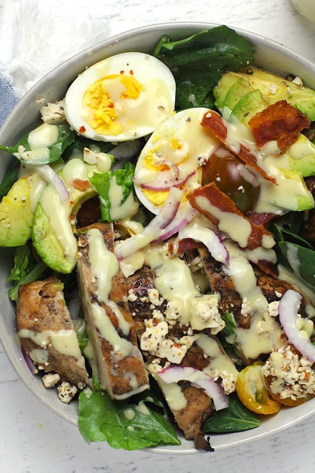 A closeup of a serving bowl of chicken Cobb Salad, with honey mustard drizzled on top.