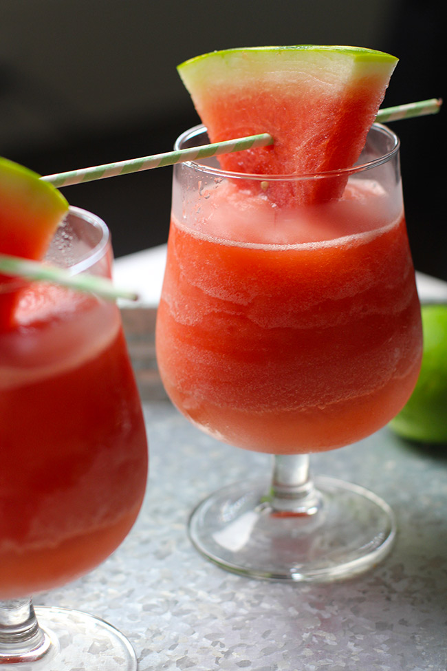 Side view of two glasses of watermelon frose, with watermelon slices for garnish.