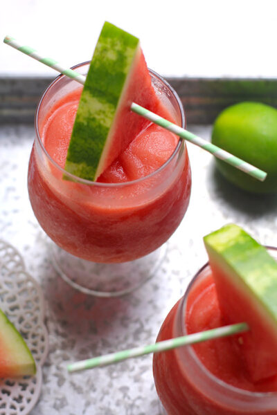 Two glasses of watermelon frose, on a gray tray with watermelon wedges for garnish.