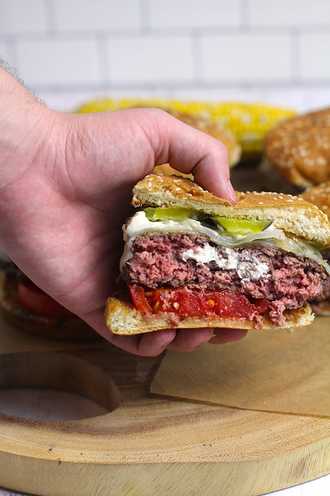 A hand holding one half of a juicy Lucy, showing the cheesy center.