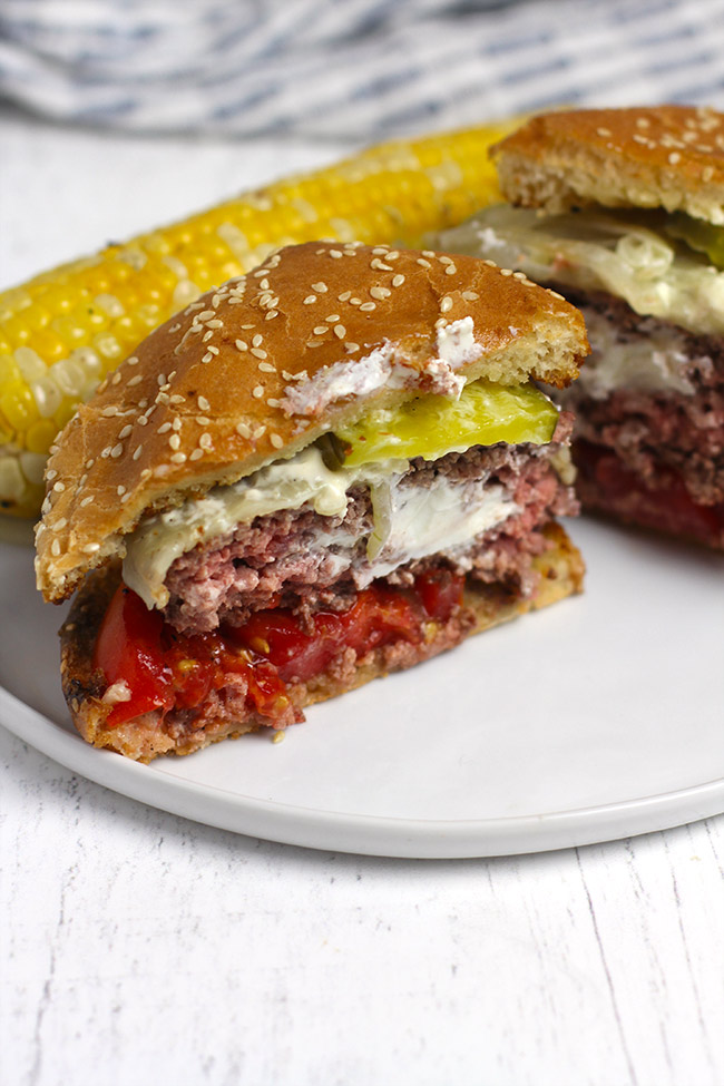 Two halves of juicy Lucy burgers on a serving plate.