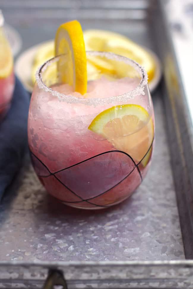Side shot of a glass of pink lemonade vodka slush, with a sugar rim and a lemon slice.