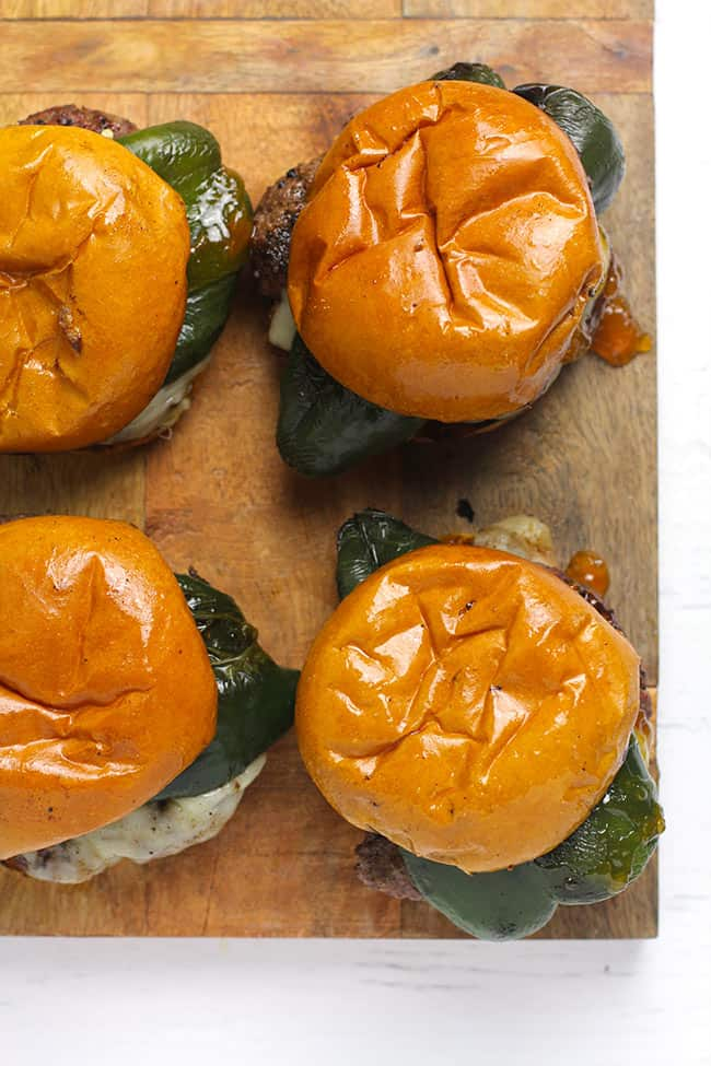 Overhead shot of four poblano burgers with apricot preserves on a wooden board.