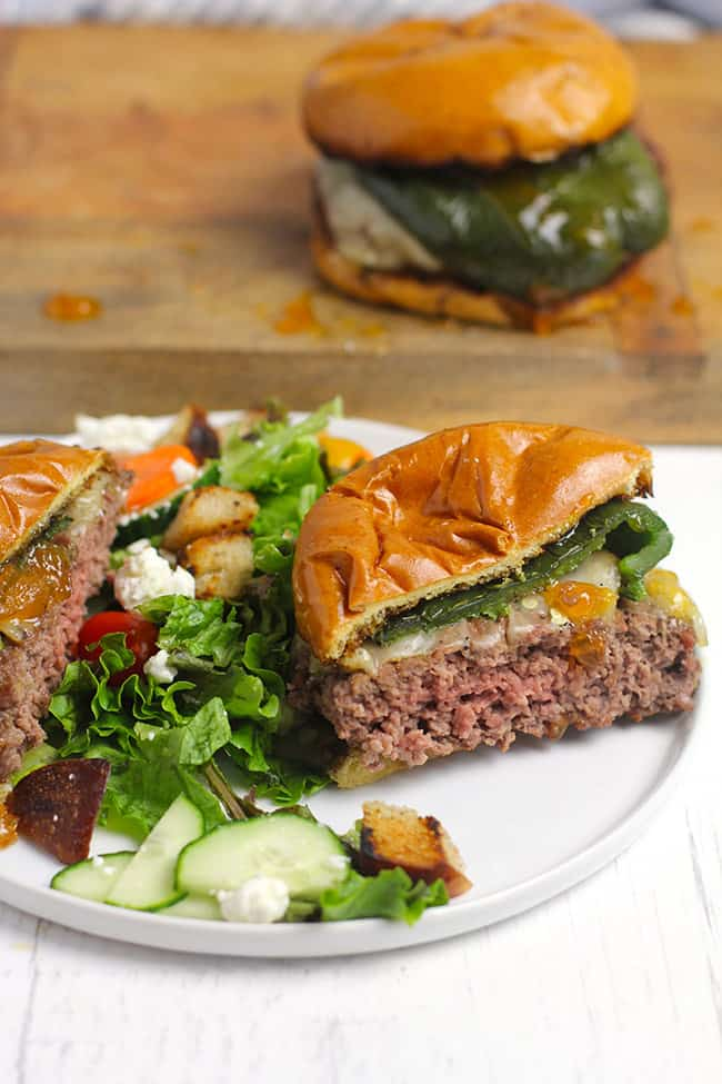 Side shot of a halved poblano burger on a white plate with salad, with a burger in the background.