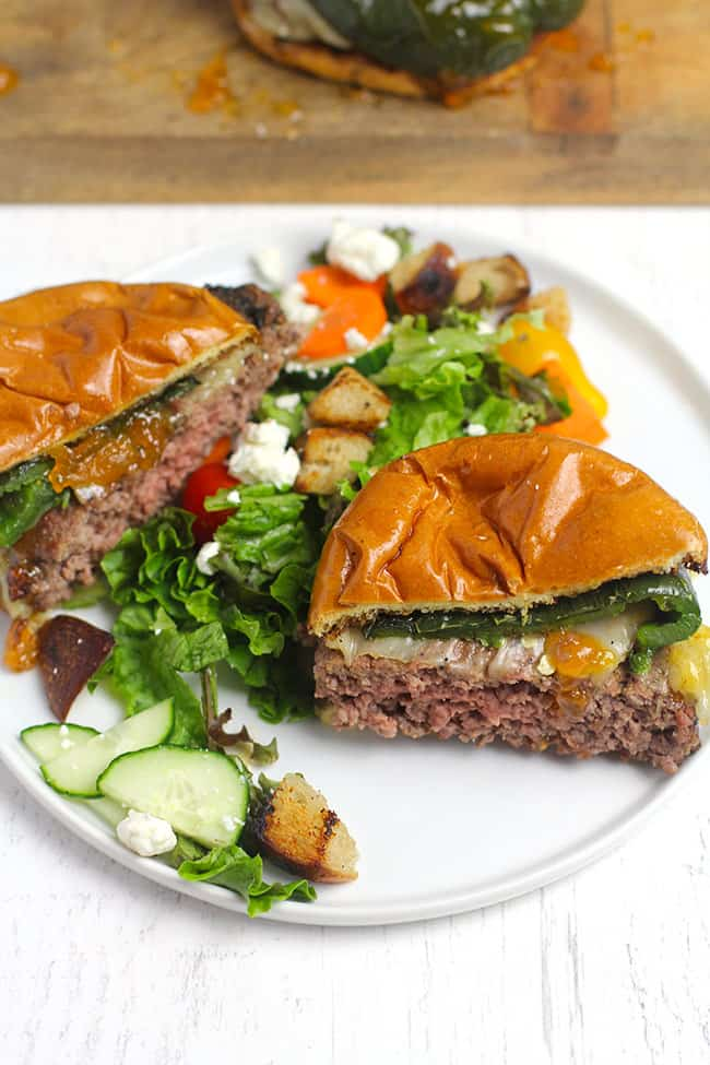 Side shot of a grilled poblano burger with apricot preserves, sliced in half on a white plate with salad.