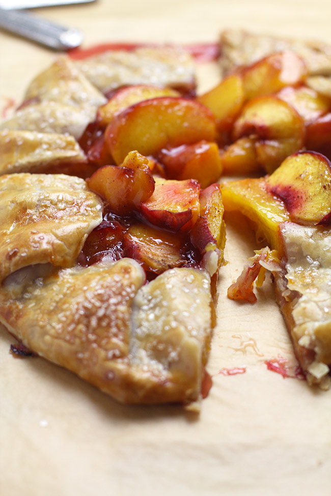 Side shot of a sliced peach galette.
