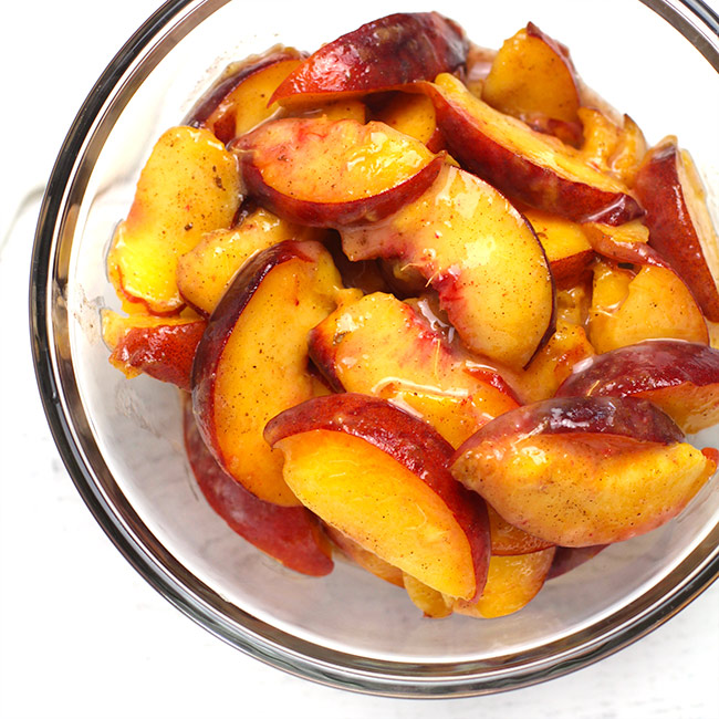 A glass bowl of sliced peaches.