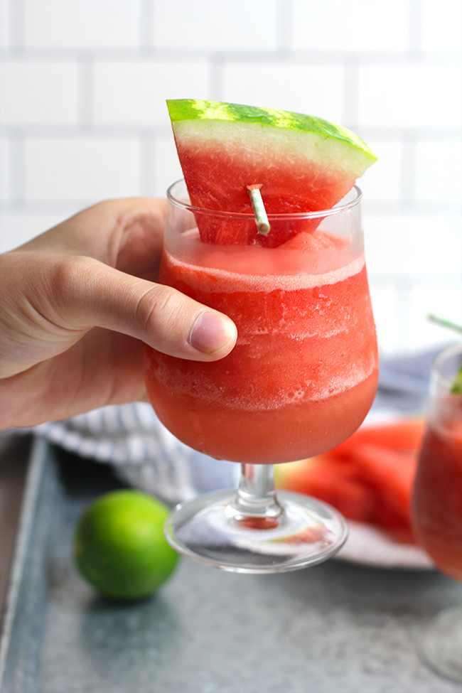 A hand holding a frozen watermelon rose, with a watermelon wedge for garnish.