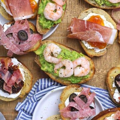 A board of four different kinds of crostini appetizers.