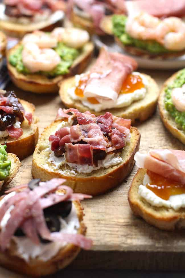 Side shot of a board of crostini, four ways.