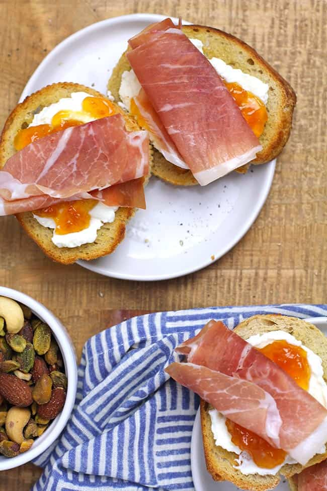 Two plates of prosciutto goat cheese crostini with apricot preserves.