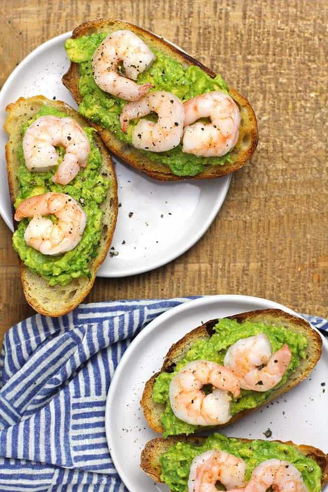 Two plates of shrimp avocado crostini appetizers.