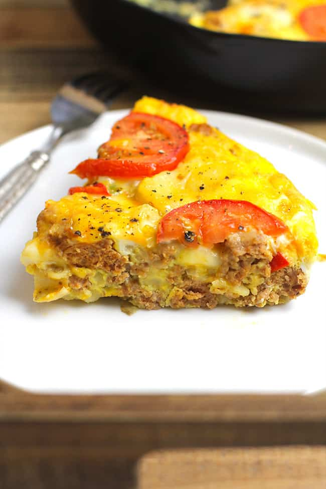 One large slice of sausage breakfast frittata with veggies on a serving plate.