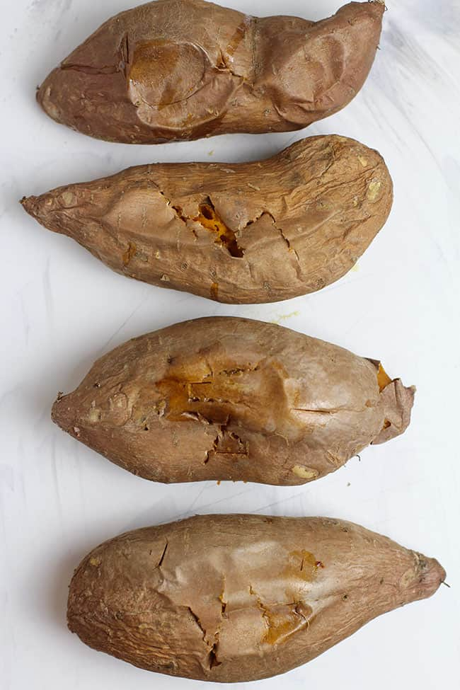 Four large baked sweet potatoes on a white board.