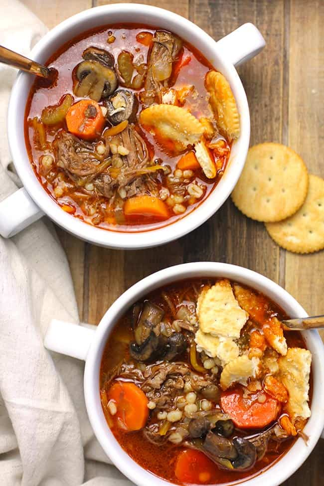 Two bowls of beef barley vegetable soup, with crackers.