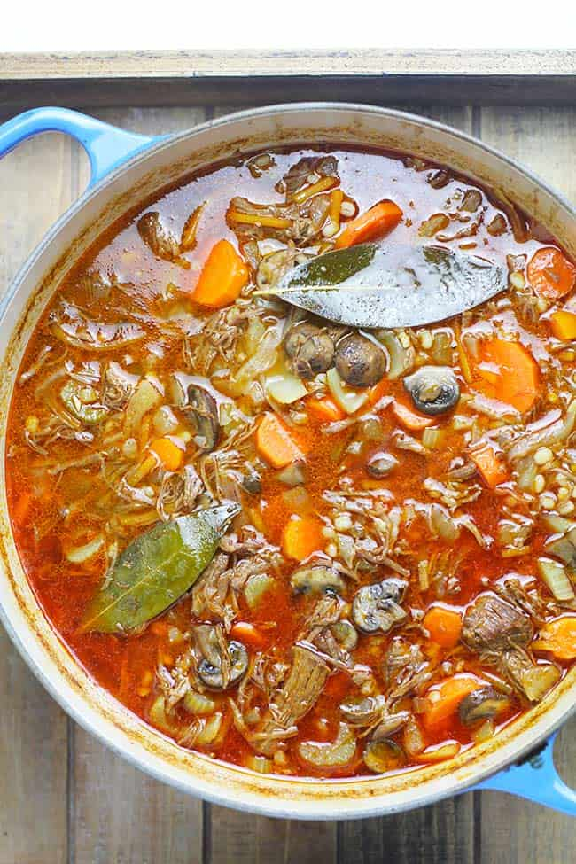 Overhead shot of a stock pot of beef barley vegetable soup, with bay leaves.