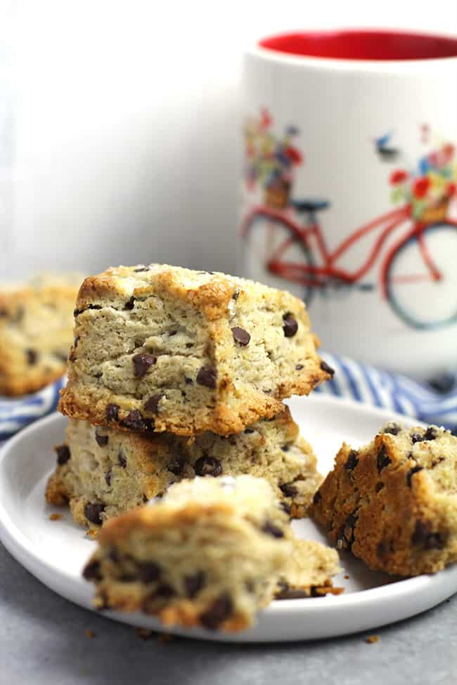 Side shot of a small plate of mini chocolate chip scones, with a biking mug in the background.