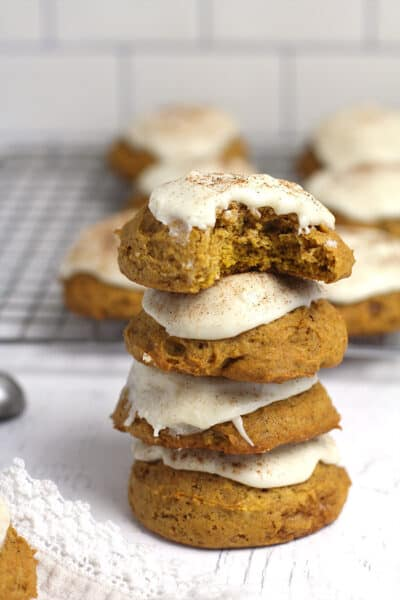 A stack of four pumpkin cookies with icing.