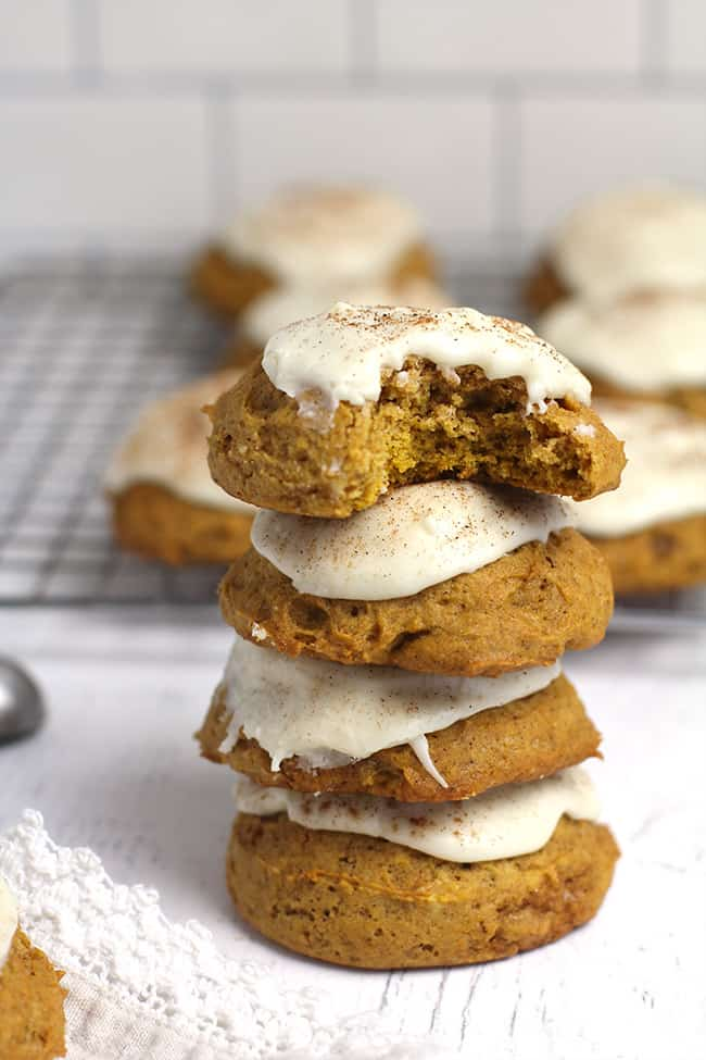 A stack of four iced pumpkin cookies.