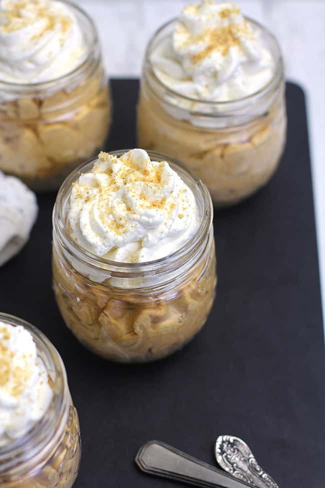 Overhead shot of several pumpkin cheesecakes, in mason jars.