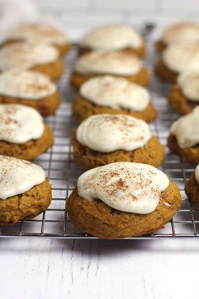 Side view of iced pumpkin cookies on a cooling rack.