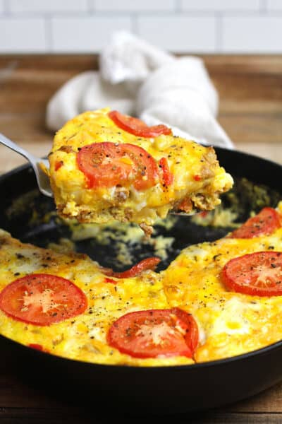 A slice of sausage breakfast frittata with veggies being lifted out of a skillet.