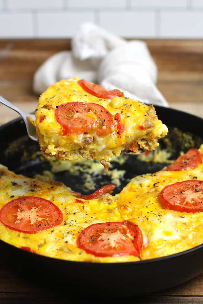 A large slice of sausage breakfast frittata being lifted out of the skillet.