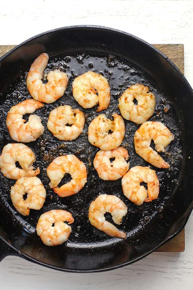 A cast iron skillet with grilled shrimp.