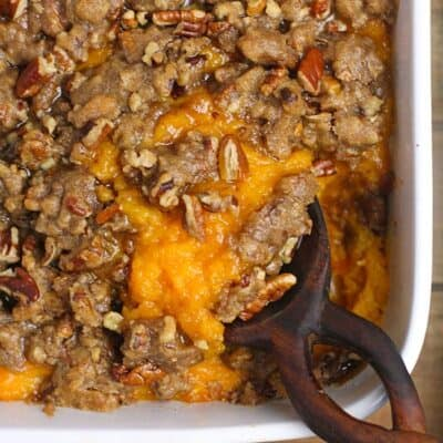 Closeup of sweet potato casserole with pecan crumble topping.
