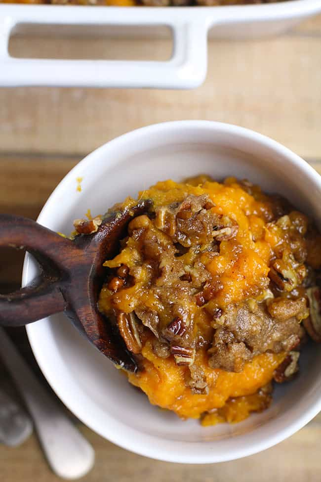 a spoonful of sweet potato casserole with pecan crumble spooned in a bowl.