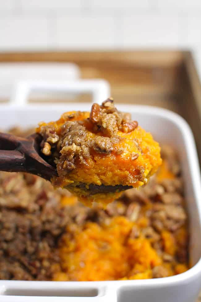 A spoonful of sweet potato casserole being lifted out of the dish.