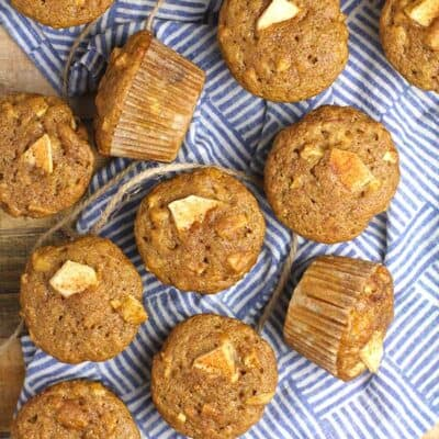 Overhead shot of applesauce cinnamon muffins on a blue and white napkin.